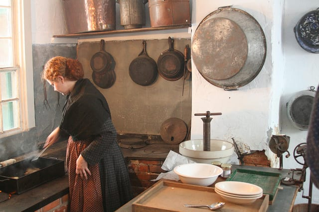 lady in period dress cooking in old-timey kitchen for communal meal