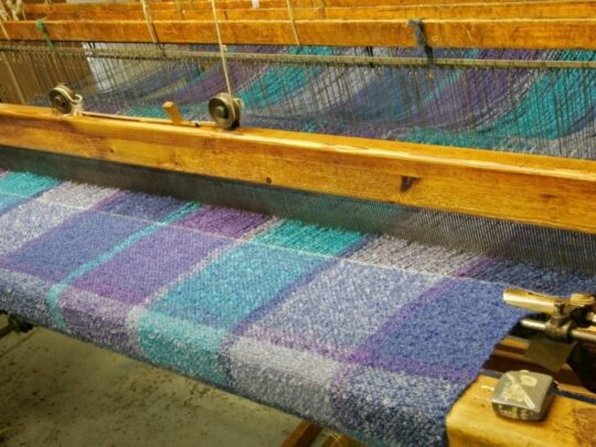 closeup of loom weaving fabric