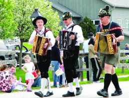 3 men walking and playing accordians at Maifest
