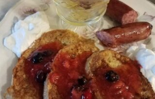 Breakfast of toast with jam, sausage and fruit