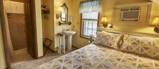 Room 9 with queen-sized bed light with bright lamps and pedestal sink