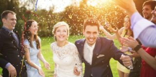 bride and groom running through guests throwing confettii
