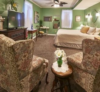 Room 5 with king-size bed, fireplace and comfy chairs