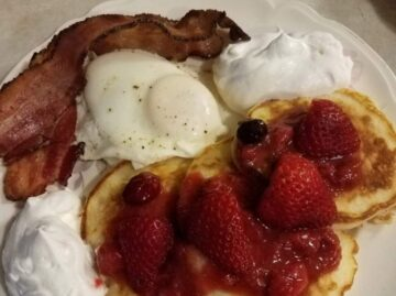Breakfast with pancakes topped with strawberries, egg and bacon