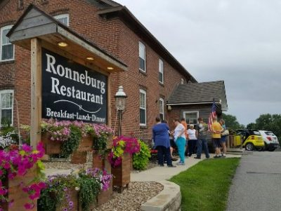Ronneburg Restaurant sign and people standing on sidewalk in front of building