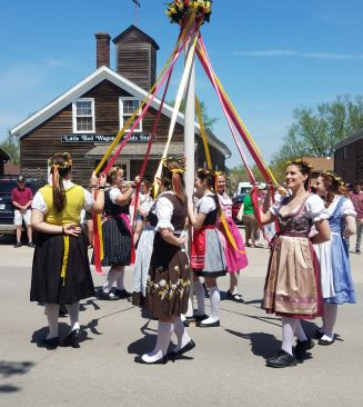 Ladies in period costume around maypole at Maifest