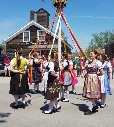 Ladies in period costume around maypole at Maifest
