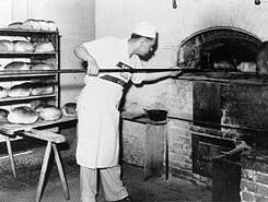 man putting bread in brick oven