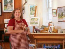 Lady artist standing near artwork